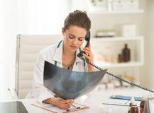 Doktorfrau mit fluorography Unterhaltungstelefon Stockfoto