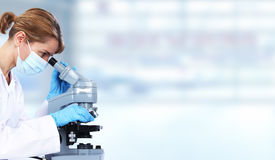 Doktorfrau mit Mikroskop stockfotos