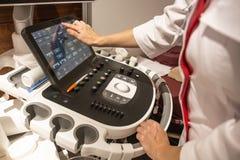 Doktorhände auf Bedienfeld mit Tastatur der Diagnoseausrüstung des medizinischen Ultraschalls in der Klinik stockfoto