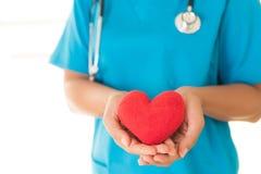 Doktorhände, die rotes Herz halten stockbild