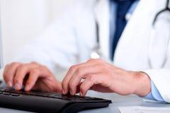 Doktorhände unter Verwendung eines Computers Stockfotos