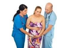 Doktorhelfen schwanger in den Schmerz Lizenzfreies Stockfoto