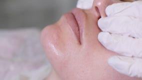 Doktorkosmetiker in den weißen Gummihandschuhen, die Gesichtsmassage tun stock video