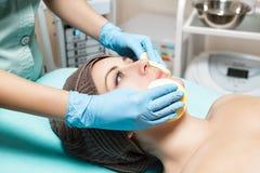 Doktorkosmetiker reinigt Hautfrau mit Schwamm Cosmetologybehandlung skincare Gesicht Blumenblatt der Rosen Stockfotos