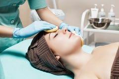 Doktorkosmetiker reinigt Hautfrau mit Schwamm Cosmetologybehandlung skincare Gesicht Blumenblatt der Rosen Lizenzfreie Stockfotografie