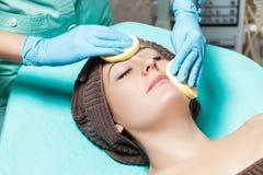 Doktorkosmetiker reinigt Hautfrau mit Schwamm Cosmetologybehandlung skincare Gesicht Blumenblatt der Rosen Stockfotografie