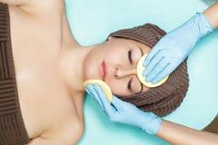 Doktorkosmetiker reinigt Hautfrau mit Schwamm Cosmetologybehandlung skincare Gesicht Blumenblatt der Rosen Lizenzfreie Stockbilder
