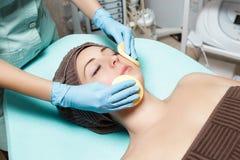 Doktorkosmetiker reinigt Hautfrau mit Schwamm Cosmetologybehandlung skincare Gesicht Blumenblatt der Rosen Stockbild
