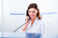 Doktorkrankenschwester mit Telefon in der Rezeption Lizenzfreie Stockbilder