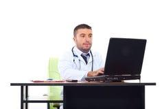 Doktormann, der auf Laptop im Büro schreibt stockbilder