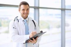 Doktormann füllt Krankengeschichteform auf Stockfoto