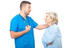 Doktormannesgegenteil mit älterem Patienten Stockfoto