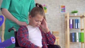 Doktormasseur, der oben Halsmassage eine Jugendlichen in einem Rollstuhlabschluß antut stock video footage