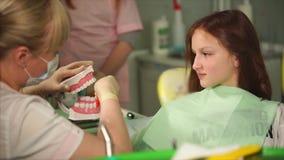 Doktorn av den tand- kliniken visar tonåringen hur man borstar riktigt hans tänder stock video