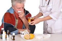 Doktorn behandlar den sjuka gamala mannen royaltyfri bild