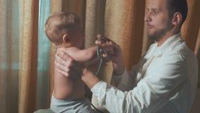 Doktorn besöker behandla som ett barnpatienten hemma behandla som ett barn det lyckliga stetoskopet arkivfilmer