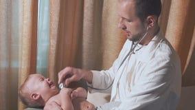 Doktorn besöker behandla som ett barnpatienten hemma Behandla som ett barn gråt och manipulera med stetoskopet arkivfilmer