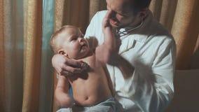 Doktorn besöker behandla som ett barnpatienten hemma behandla som ett barn stetoskopet arkivfilmer