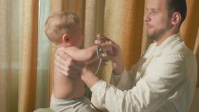 Doktorn besöker behandla som ett barnpatienten hemma behandla som ett barn stetoskopet stock video