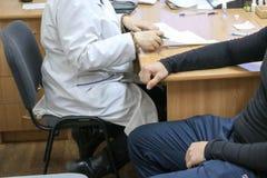 Doktorn den medicinska arbetaren i ett vitt lag råder patienten av en sjuk man som sitter på en stol i en medicinsk institution royaltyfria foton