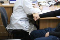 Doktorn den medicinska arbetaren i ett vitt lag råder patienten av en sjuk man som sitter på en stol i en medicinsk institution royaltyfria bilder