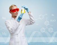 Doktorn för den unga kvinnan räcker den Erlenmeyer flaskan arkivfoto