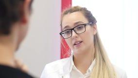 Doktorn för den unga kvinnan talar till den tålmodiga närbilden lager videofilmer