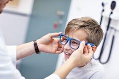 Doktorn för optiker för optometrikern för barnoptometry undersöker den manliga synförmåga av pysen arkivfoto