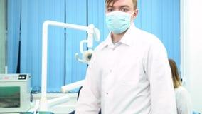 Doktorn förbereder sig för det kommande tillvägagångssättet och bär den skyddande maskeringen med hans assistent som talar  stock video
