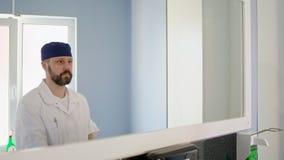 Doktorn förbereder sig till kirurgi i ett sjukhus, genom att sätta på det medicinska locket och maskering stock video