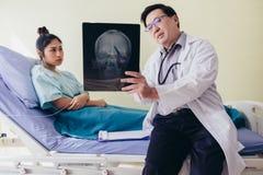 Doktorn förklarar om hjärnröntgenstråleresultaten till en kvinnlig patient som ligger i säng på ett sjukhus arkivbild