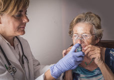 Doktorn förklarar till den gamla kvinnan hur arbeten för ventimaskinandningutbildning Royaltyfri Foto