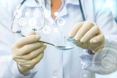 Doktorn fyller in en sked av medicin Royaltyfri Fotografi