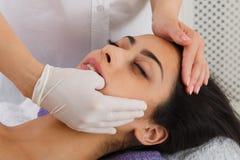 Doktorn gör Intra muntlig massage i brunnsortwellnessmitt royaltyfri foto