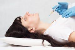 Doktorn gör plasma-lyftande injektionen till flickan i halsen mot skrynklor och för härlig hud, plasma royaltyfri foto