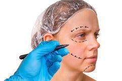 Doktorn gör prickiga linjer på den kvinnliga framsidan för kosmetisk framsidaelevator Arkivbild