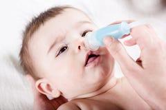 Doktorn gör ren näsan av lite behandla som ett barn Royaltyfri Fotografi