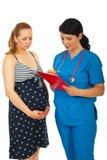 doktorn ger det gravida recept till kvinnan Royaltyfria Foton