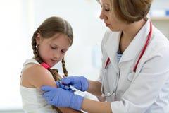Doktorn ger injektionen till armen för flicka` s royaltyfria foton