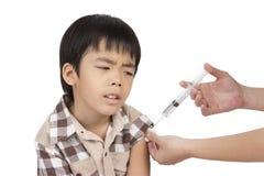 Doktorn ger injektionen till pojken Royaltyfria Bilder