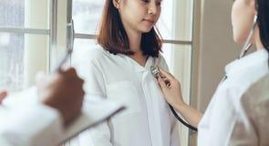 Doktorn ger konsultation med patienten och antecknar behandlinghistorien grundligt arkivbild