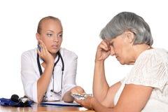 Doktorn ger preventivpillerar till hennes patient Royaltyfri Bild