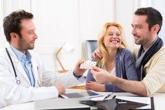 Doktorn ger preventivpillerar till par av patienten Arkivbild