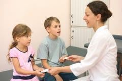 Doktorn ger tablets för syskongrupp Royaltyfri Foto