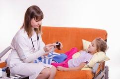 Doktorn häller en sked av medicin för att ge det sjuka barnet Royaltyfri Fotografi