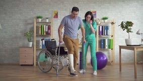 Doktorn hjälper en man att få upp med en benskada från en rullstol efter en skada stock video
