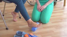 Doktorn hjälper en tonårs- flicka i en rullstol med ortopediska problem att göra övningar för att korrigera plan fot för att stän lager videofilmer