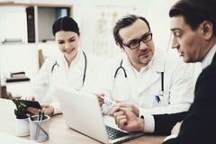 Doktorn i exponeringsglas råder tålmodigt sammanträde på tabellen med bärbara datorn i medicinskt kontor arkivfoto