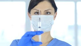 Doktorn i hållande injektion för maskering, ordnar till för att injicera Arkivbild