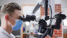 Doktorn in i medicinsk maskering ser i okular av mikroskopet i laboratorium lager videofilmer